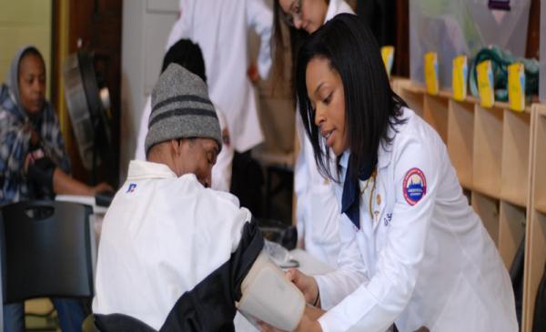 Student checking child's blood pressure